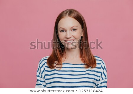 Headshot of pretty smiling European woman with charming smile, wears striped jumper, has brown hair, Stock photo © vkstudio