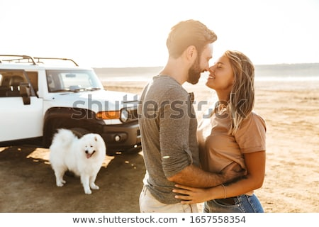 Stock photo: Woman hugging dog samoyed outdoors at the beach in car.