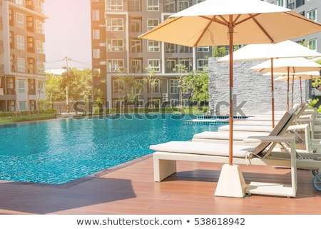 Seat and chairs on deck by swimming pool Stock photo © backyardproductions
