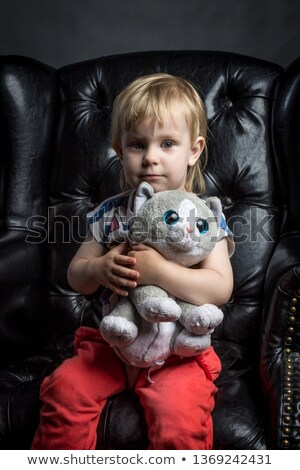 Pretty blond girl in red leather chair Stock photo © MikLav