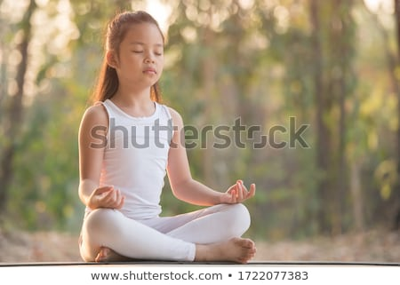 young girl practicing yoga green blurred background stock photo © nobilior