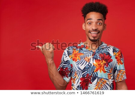 attractive smiling man pointing left to copy space stock photo © scheriton