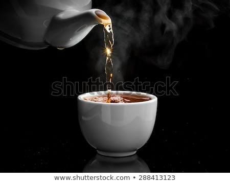 pours tea into a cup stock photo © Peredniankina
