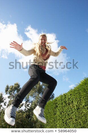 Young Woman Jumping On Trampoline Caught In Mid Air Stock photo © monkey_business