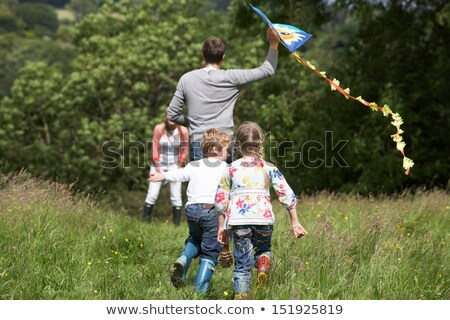 rear view of family flying kite in countryside stock photo © monkey_business