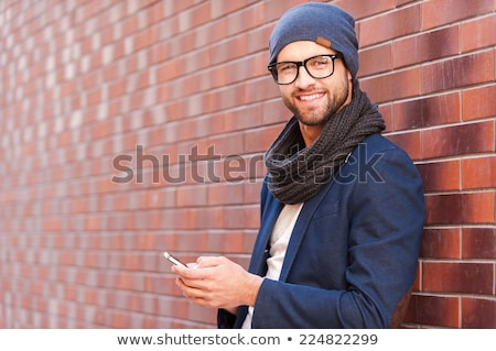 young casual man smilling, leaning on a brick wall  Stock photo © feedough