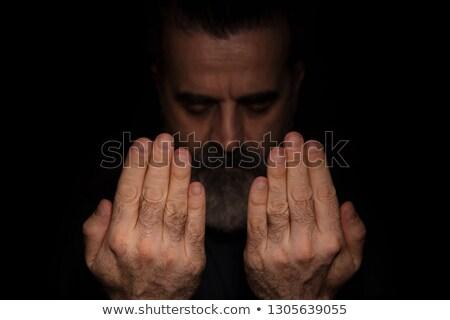 adult bearded man praying in dark room stock photo © stevanovicigor
