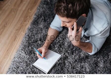 homme · notepad · parler · téléphone · portable · haut · vue - photo stock © deandrobot