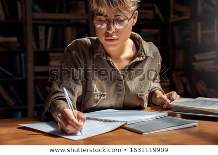 Serious caucasian student in library learning education material Stock photo © deandrobot