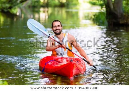 Junger Mann, der im Fluss Kajak fährt Stock foto © Kzenon