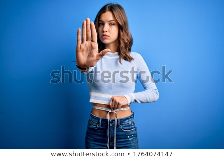 Portrait of beautiful blond woman with warning tape stock photo © konradbak