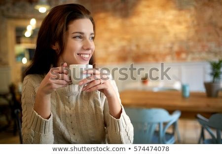 Smiling pretty woman sitting at the cafeteria and drinking coffee Stock photo © deandrobot