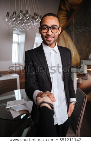 vertical image of smiling african man holding arms in pockets stock photo © deandrobot