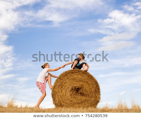 Stock photo: girl helping woman to climb hay bale