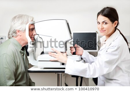 Female optometrist taking eye test of young patient Stock photo © wavebreak_media