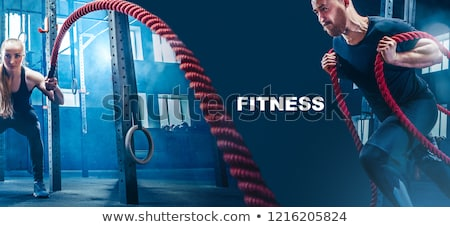 Stock photo: Strong woman exercising with battle ropes during functional training