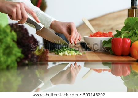 womans hands cut yellow pepper on a wooden board on the kitchen table cooking salad stock photo © artjazz