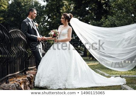 Groom hugs bride tender while wind blows her veil Stock photo © ruslanshramko