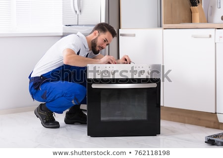 male technician fixing oven stock photo © andreypopov