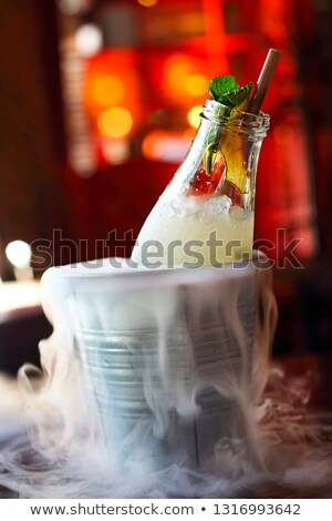 Lemonade serviced in the bottle with mint in the bucket with dry Stock photo © dashapetrenko