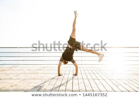 young sports man make exercises yoga on the beach stock photo © deandrobot