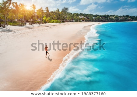 Aerial view of the running young woman on the sandy beach Stock photo © denbelitsky