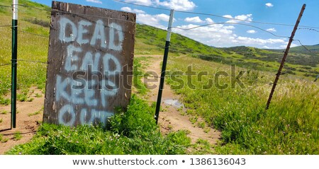 Stock photo: Dead End Keep Out Sign On Wire Fence At Dirt Road