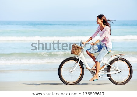 girl riding bicycle on the beach stock photo © jossdiim