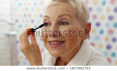 Uśmiechnięty starszy kobieta lustra tusz do rzęs Zdjęcia stock © dolgachov