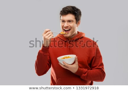 smiling young man in red hoodie eating cereals Stock photo © dolgachov