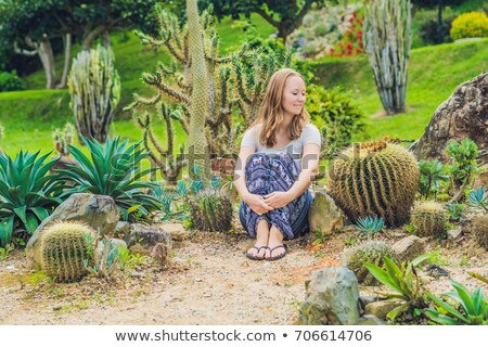 A young woman sits on the ground among the cactus. Spiny concept. Out of comfort zone concept Stock photo © galitskaya