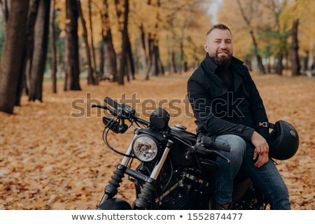 Bearded male motorcyclist rides black bike, holds helmet, has travel on his own transport, poses in  Stock photo © vkstudio
