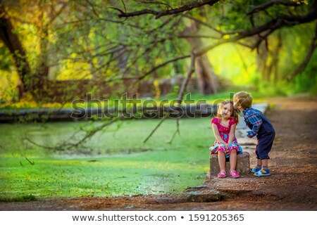 Brother and sister walking near an artificial lake under the branches of trees Stock photo © ElenaBatkova