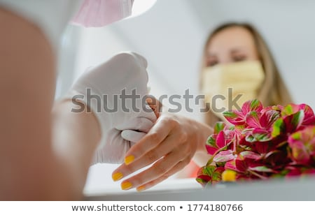 Customer in nail art studio wearing a protective face mask Stock photo © Kzenon