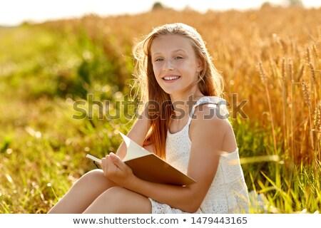 Sonriendo nina lectura diario cereales campo Foto stock © dolgachov