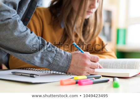 Confident adult teacher helping to students  in school classroom Stock photo © HASLOO