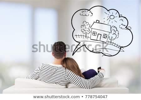 Foto stock: Young Couple Sitting On Sofa And Dreaming