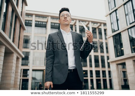 Young man holding laptop near his face outdoor stock photo © HASLOO