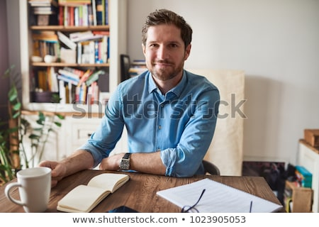 Portrait of young man sitting indoors at his office and working. stock photo © HASLOO