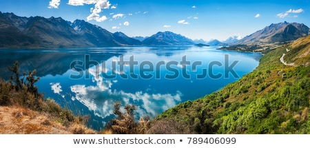 Landscape of snow-capped mountains at lakeside Stock photo © bbbar