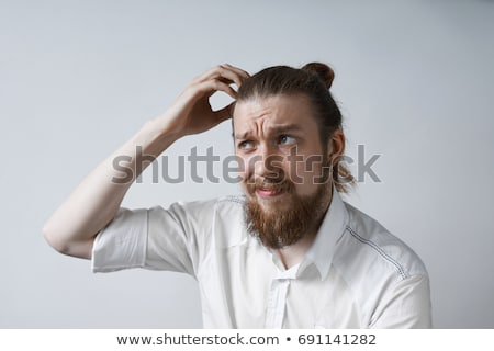 Puzzled man scratches his head, isolated on white Stock photo © pzaxe