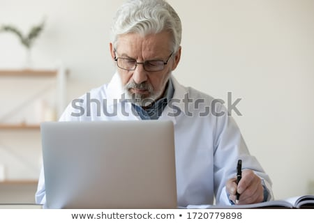 Older man making notes in a file Stock photo © photography33