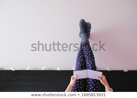 Young attractive woman lying down with her legs crossed against a white background Stock photo © wavebreak_media