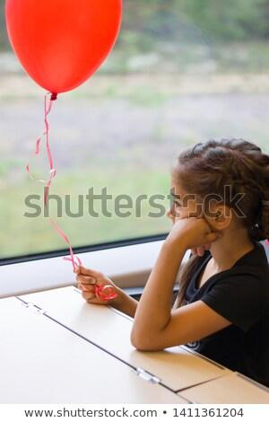 thoughtful little girl leaning on the balloon stock photo © konradbak