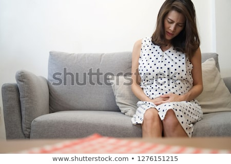 Woman Suffering From Stomach Ache Sitting On Sofa Stock photo © AndreyPopov