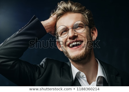 smiling elegant man posing in dark studio closing his jacket  Stock photo © feedough
