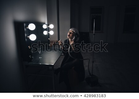 Blonde woman in black coat applying lipstick in dressing room Stock photo © deandrobot