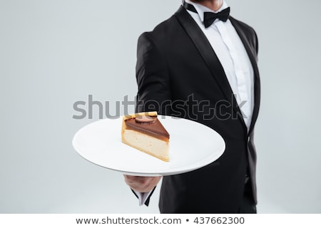 Butler in tuxedo holding piece of cake on plate Stock photo © deandrobot