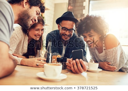 women in cafe showing pictures on smart phone stock photo © kzenon