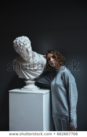 Stock photo: Young woman standing near bust